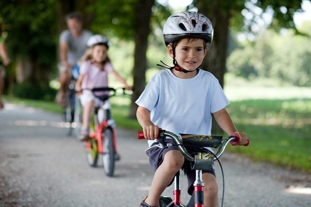 4 years old boy riding a bicyle in front of his family on a gravel path in a park