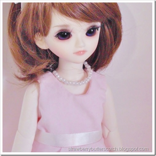A pink vintage style dress set for a doll complete with pearl necklace.