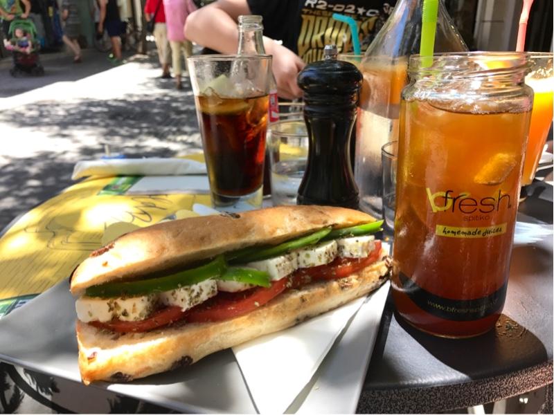 Et brød delt på langs og fylt med fetaost, paprika og tomater. Ved siden av står et høyt glass med en lysebrun drikke.