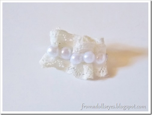 A hair clip for a doll made with pretty gathered lace and flat back pearls glued down the center.
