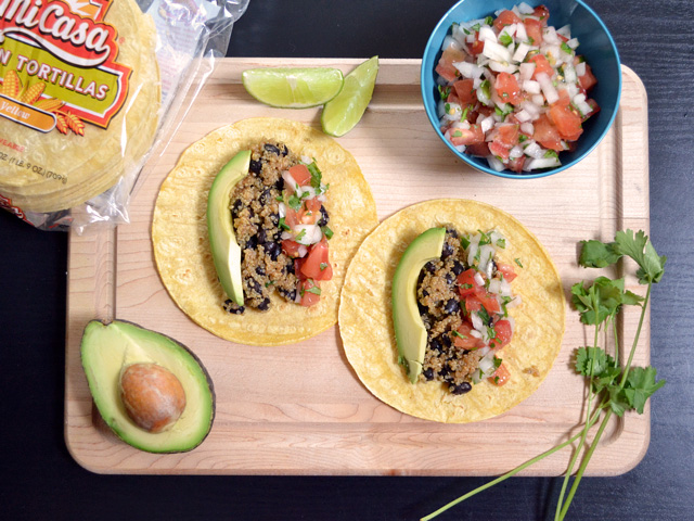 Top view of two Quinoa Black Bean Tacos on cutting board, package of tortillas, bowl of pico, half of an avocado, lime slices and cilantro on the side