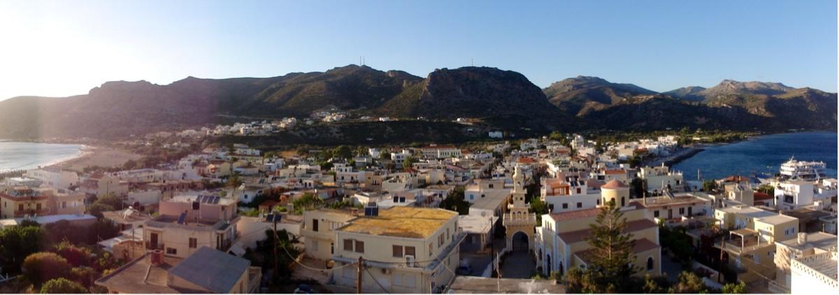 Panoramabilde av en by med lave, hvite bygninger og havet på begge sider. Fjell i bakgrunnen.