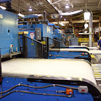 This is one of our off line die cutting machines that cuts and scores more complex patterns into our laminated solid fiber products.