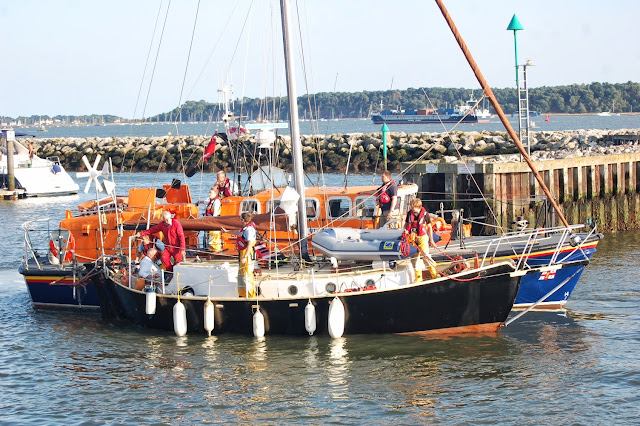 Coxswain Jonathan Clark bringing the yacht astern (in reverse) into Poole Quat Boat Haven with the crew ready with the mooring lines. 22 August 2013 Photo credit: RNLI/Dave Riley