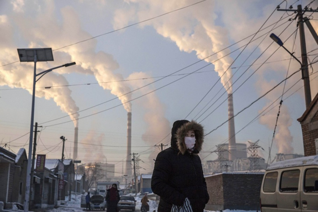 Smoke billows from stacks as a Chinese woman wears as mask while walking in a neighborhood next to a coal-fired power plant on 26 November 2015 in Shanxi, China. Photo: Kevin Frayer / Getty Images