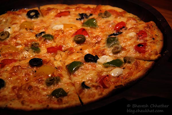 Close-up of Thin-crust Global Goodness Pizza served at Toss Sports Lounge Koregaon Park