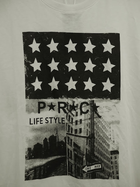 "shirt with stars resembling the U.S. flag and scenes appearing to be from the U.S. with the text ""PRC LIFE STYLE"""