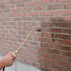A-Tech Masonry and Brick Sealer siloxane water repellent being applied to a vertical brick wall. After application the brick and mortar joints will be water repellent.