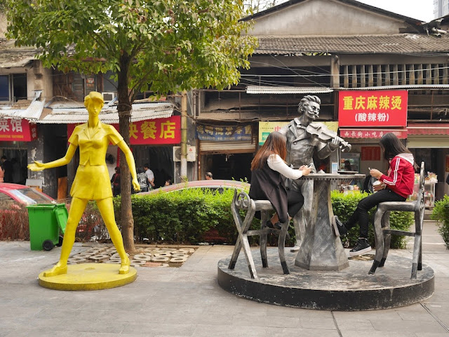 two females using mobile phones and sitting on chairs which are part of sculpture
