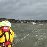 An ALB crew member looks back at the yacht under tow, which is steadied by having its mast halyard secured to the ILB - 27 October 2013. Photo credit: RNLI Poole