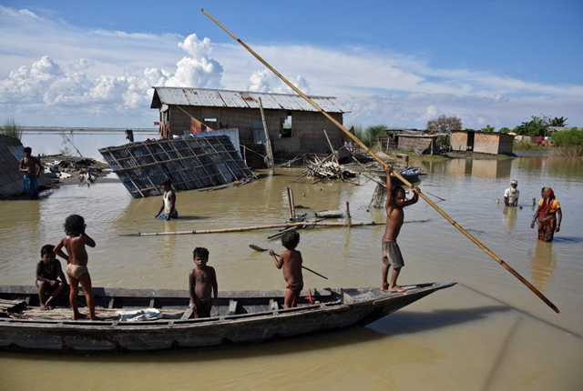 Children row a boat through floodwaters in the Morigaon district in the northeastern state of Assam, India on 20 August 2017. Photo: Anuwar Hazarika / Reuters