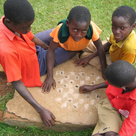 Boys in Uganda playing draughts using stones as counters
