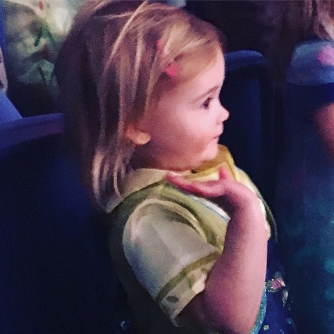Little Anna watching frozen on ice and waving to her favourite characters