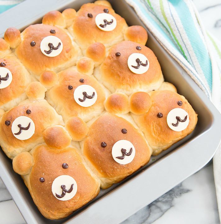 a overhead photo of bear-shaped rolls in a baking pan