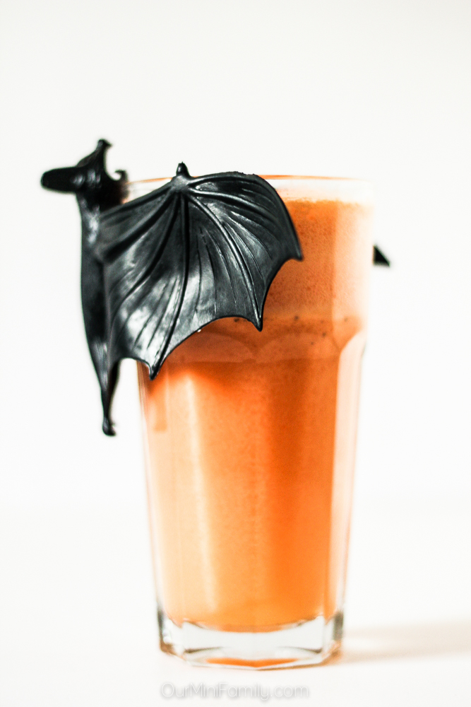 halloween orange shake with decorative bat on the glass