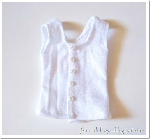 "A white doll sized tank top with faux pearl ""buttons"" down the front.  The button front is fake, the top opens in back with velcro."