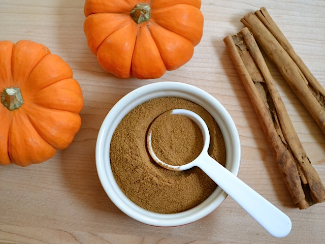 Homemade Pumpkin Pie Spice in a small bowl with a measuring spoon and cinnamon and pumpkins near by