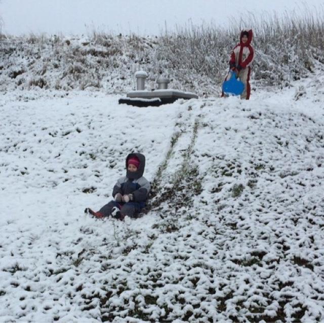 Kinder rutschen mit Poporutscher einen Hügel herunter