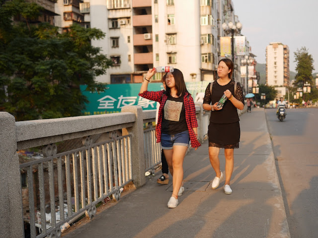 young women walking on a bridge and looking upwards in Shaoguan