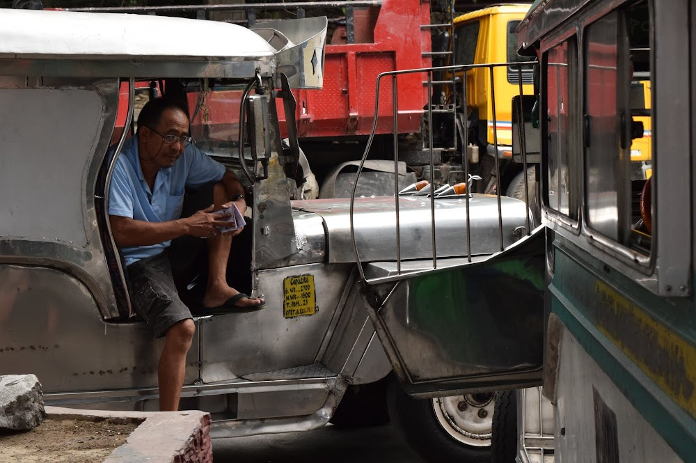 A Jeepney driver taking a break.  Most of the Jeepneys are very colourful and highly modified, remind me of buses in some Latin American countries.