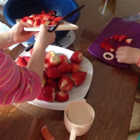 Kinder schneiden Erdbeeren