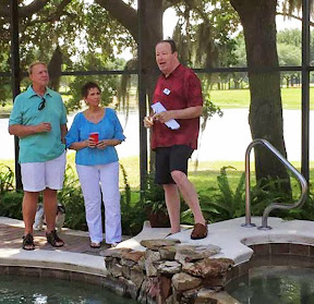 Dan Steinwald (in the red shirt) standing next to his pool while he acknowledges the special contribution made by Jerry and Peg to the group