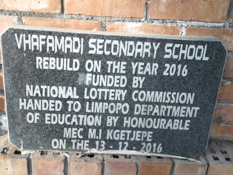 This plaque was unveiled during Vhafamadi High School's official opening in December 2016. The shoddy workmanship is clear from this photo, including the fact that the plaque has not even been cemented permanently in place almost two years later.