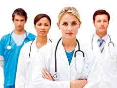 Portrait of confident professional doctors standing in hospital over white background