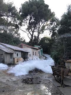 Vann som fosser nedover en sliten gate med gamle hus.
