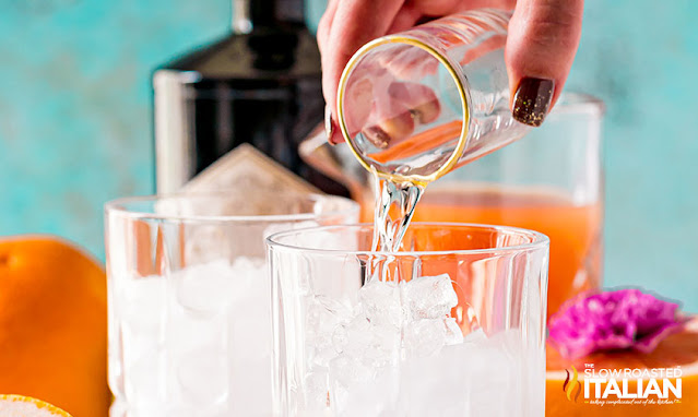 greyhound drink pouring the gin in a glass over ice