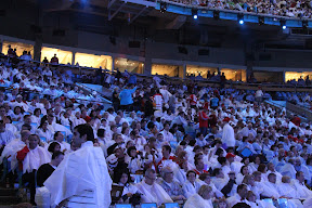 Audience members in their white and light blue ponchos