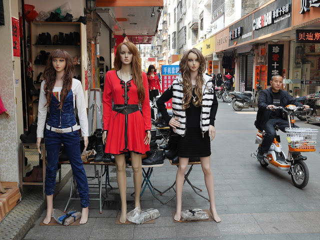 mannequins and man on a small electric bike in Yangjiang, China