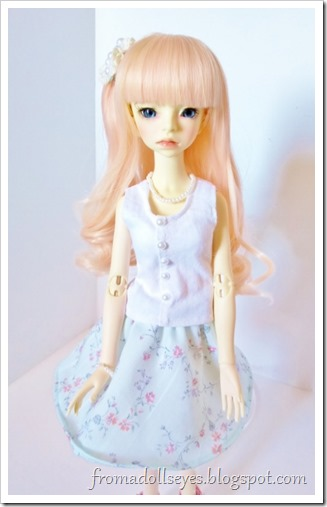 "A pretty ball jointed doll wearing her new hand made outfit.  A white tank top with ""buttons"" down the front, a floral print skirt, a lacey hair clip and a pearl necklace with matching bracelet."