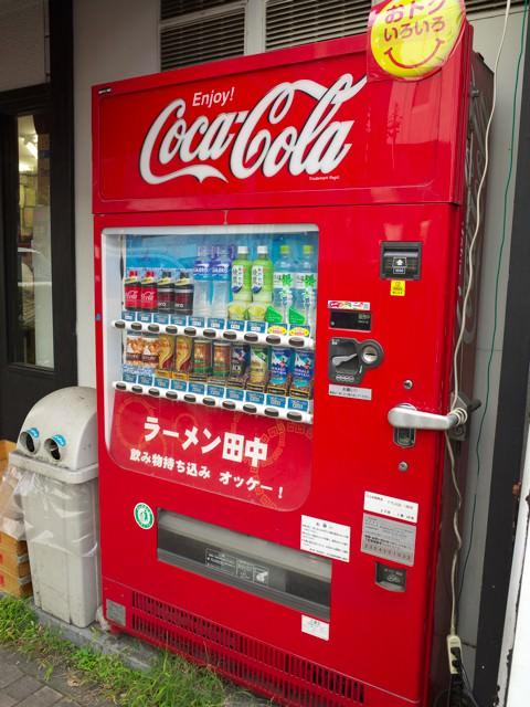 店頭に置かれた「ラーメン田中」の文字が入った自販機。「飲み物持ち込みオッケー!」と書かれてる。