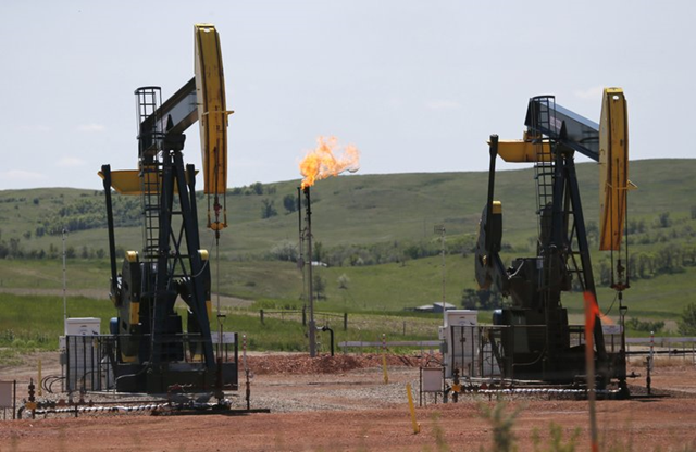 In this 12 June 2014 file photo, natural gas is burned off near pumps in Watford City, N.D. As Trump rolls back some Obama-era rules on climate-changing methane pollution, Colorado officials say their regulations have reduced oil field leaks. A report released Thursday, 23 August 2018, shows required state inspections helped find and repair 73,000 methane leaks over three years. Photo: Charles Rex Arbogast / AP Photo