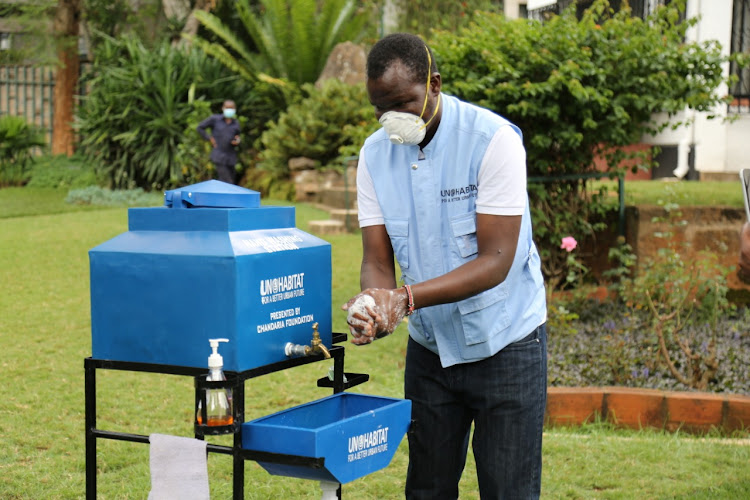 A man washes hands at hand washing station donated to Kibera residents by the UN Habitat.
