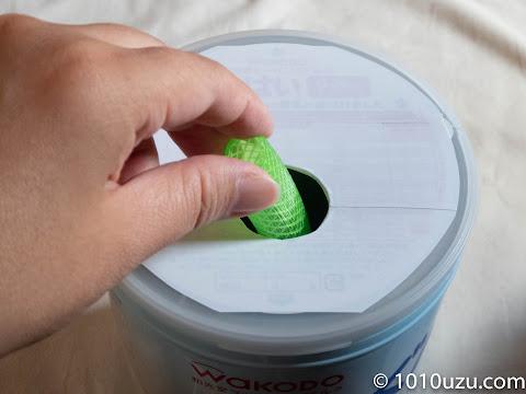 ミルク缶のフタに穴にホース落として遊べる