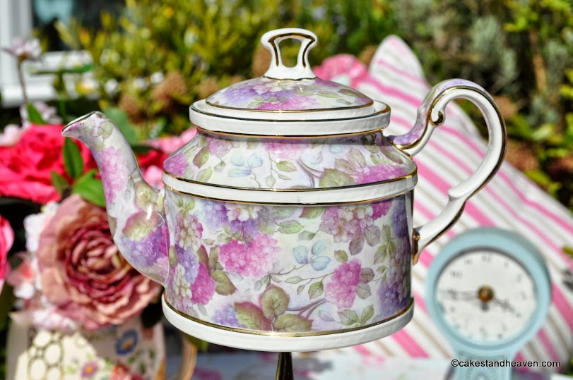 lilac and pink bone china teapot on a cake stand