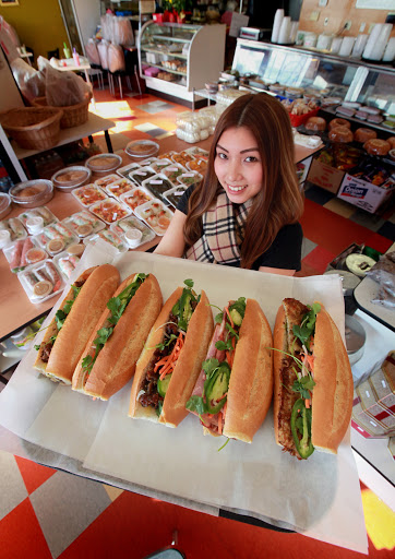 TONY'S BAKERY & DELI   Jacklyn Tran, sister of Tony of Tony's Bakery & Deli in Rainier Valley, holds a tray of banh mi (Vietnamese sandwiches).  From left to right, the sandwiches are:  beef stew, tofu, grilled pork, combo cold cuts and white fish. [Seattle Times Ellen Banner]