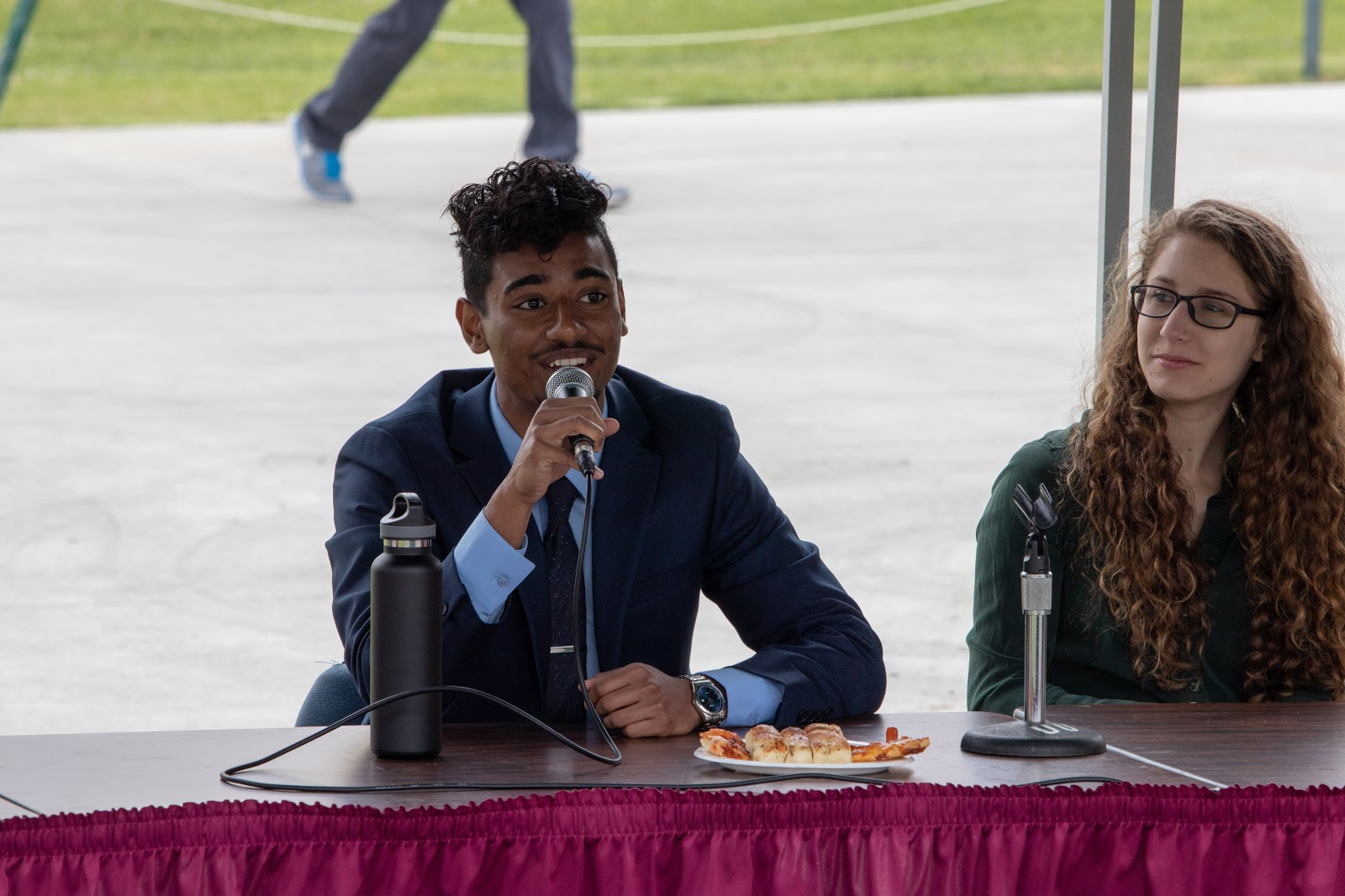 ASI President, Jenny Greenberg, and ASI Vive President at last year's Pizza With the Candidates speaking into two microphones