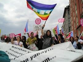 Demonstranten mit Trommel, Plakaten und Regenbogen-Friedensfahne.