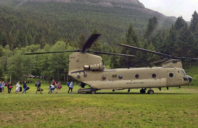 In this photo provided by the Montana Army National Guard, middle school students from the Montana Wilderness School of the Bible, attending a Bible camp along the Rocky Mountain Front, are guided onto a Chinook helicopter Thursday, 21 June 2018. The campers were flown to Great Falls after flooding earlier this week washed out the road to the camp. Photo: Montana Army National Guard / The Associated Press