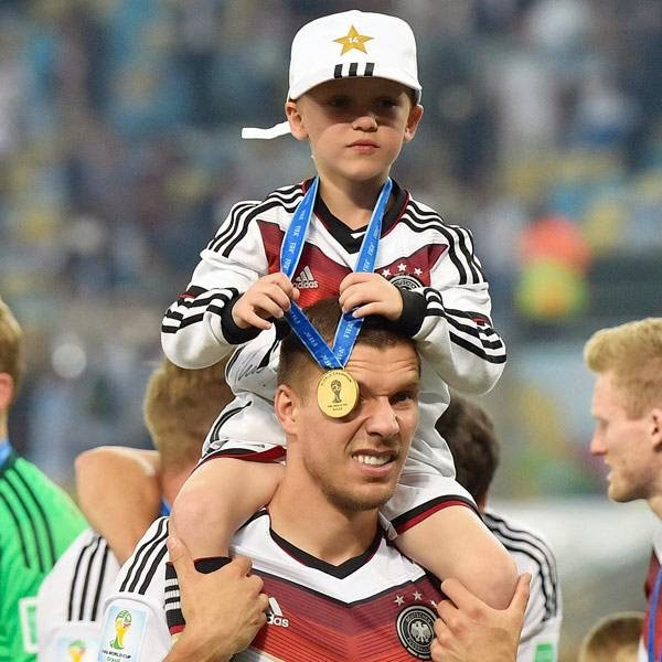 Germany's Lukas Podolski celebrates with his son during a victory lap after the World Cup final soccer match between Germany and Argentina at the Maracana Stadium in Rio de Janeiro, Brazil, Sunday, July 13, 2014.