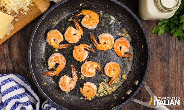 alfredo pasta with shrimp - cooked shrimp in a skillet