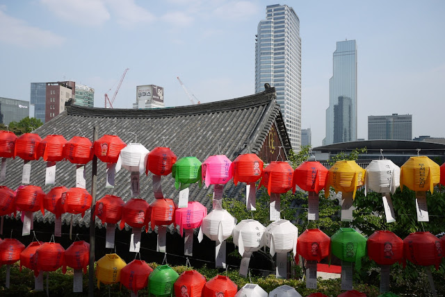 lanterns at Bongeunsa Temple with city skyline in the background