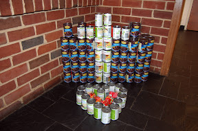 Love for the Cross  (cross make out of fruit cocktail cans against a background of black beans, heart filled in with cans of tomato sauce)