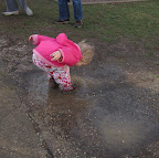 Young child splashing in a puddle.