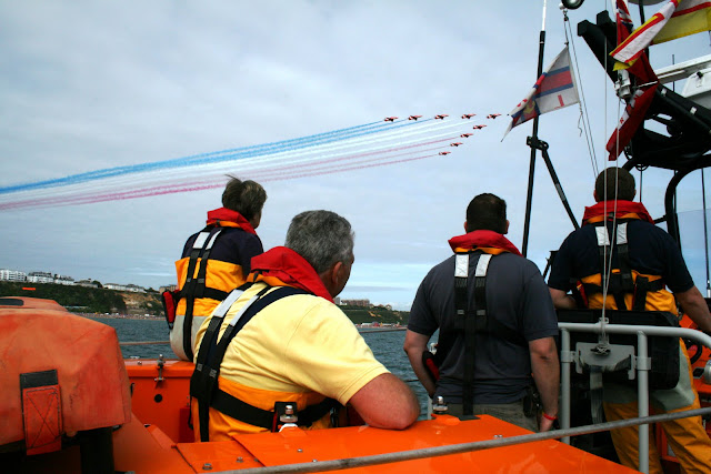 Poole all-weather lifeboat crew enjoying the Red Arrows at the Bournemouth Air Show