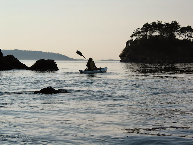 Peace and serenity envelop a kayaker paddling past Chuckanut formations. / Credit: Peter James Photography Studio