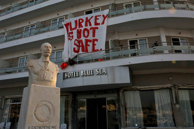 A banner reading 'Turkey is not Safe' hangs from a hotel as migrants are escorted by EU border agency officers to ferries in Mytilene, on the Greek island of Lesbos, 4 April 2016. Photo: Orestis Panagiotou / EPA